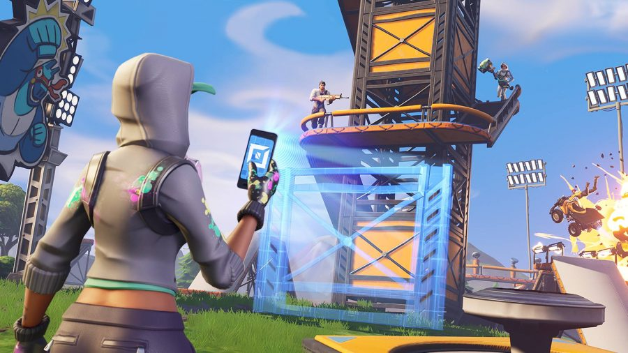 A hooded character holds a phone, which is projecting schematics for a building in front of them