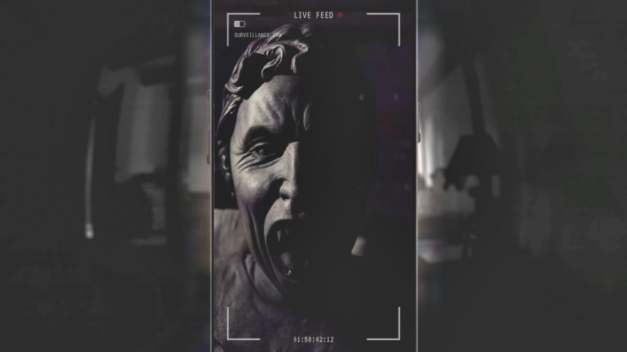 A dark figure seen through a phone screen