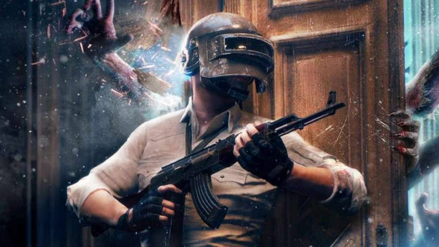 A character wearing a welding mask and holding a large gun, is pushing a door with their back, trying to stop zombified hands getting through