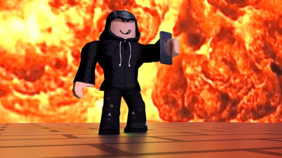 A man walking through flames holding a phone