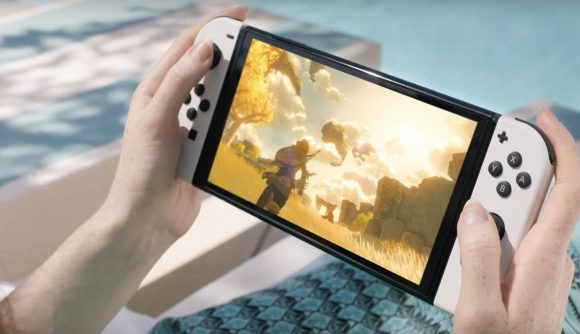 A person is sitting on a deckchair playing the new Nintendo Switch OLED Model and the sequel to Breath Of The Wild