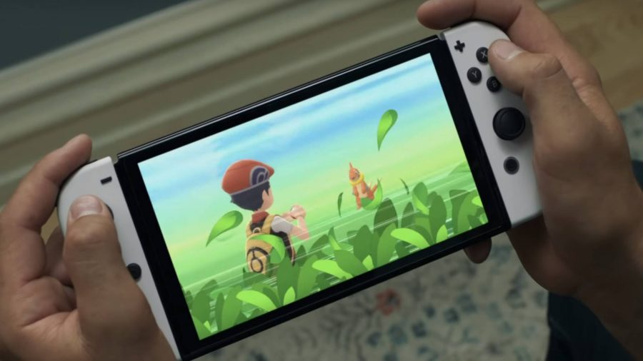 A Nintendo Switch OLED Model is being held and Pokemon Brilliant Diamond appears on screen