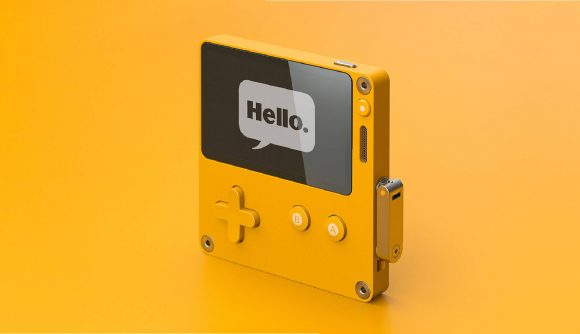 A Playdate console stands up against a yellow background