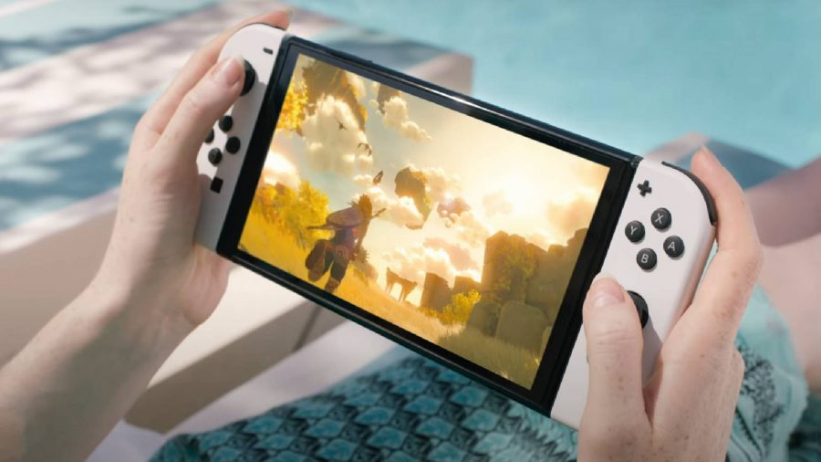 A pair of hands are holding up the Nintendo Switch OLED model, while Breath Of The Wils 2 is being played on the screen