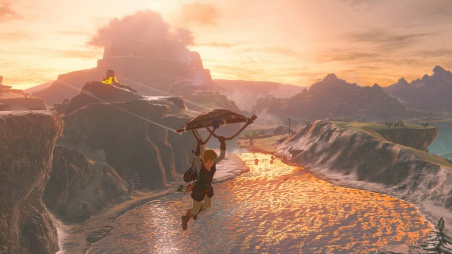 Link glides away from a cliff, over a lake lit beautifully by the setting sun. The landscape is lit up a glowing red colour